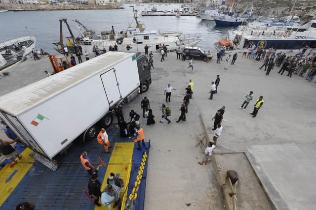 Migrants board a ship heading to Sicily, in Lampedusa, Italy, Friday, Oct. 4, 2013. A boat carrying African migrants toward Italy caught fire and capsized off the Sicilian island of Lampedusa Thur ...