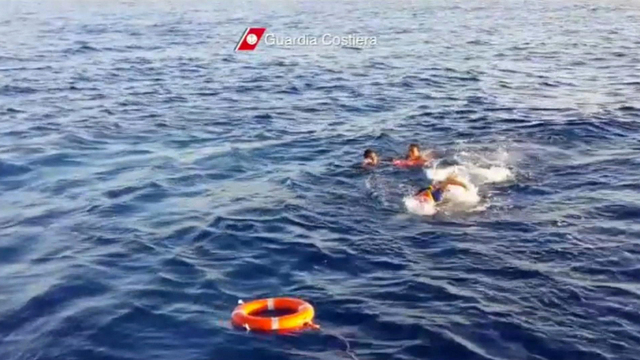 In this image made from video provided by the Italian Coast Guard and recorded on Thursday, Oct. 3, 2013, a rescuer jumps into the water to retrieve survivors of a ship transporting hundreds of mi ...