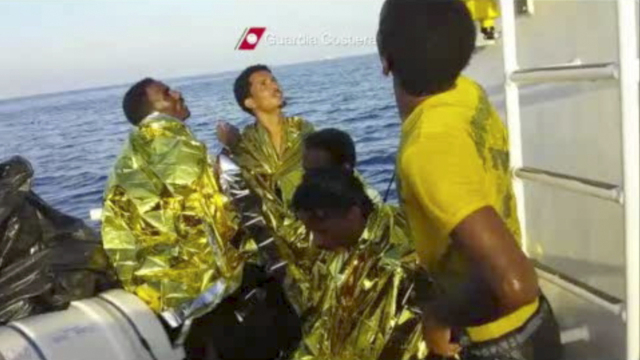 In this image made from video provided by the Italian Coast Guard and recorded on Thursday, Oct. 3, 2013, survivors of a ship transporting hundreds of migrants which caught fire and sank wear ther ...