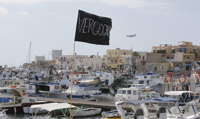 "A black flag with writing reading in Italian ""Vergogna"" (shame) waves in the harbor of the island of Lampedusa, southern Italy, Friday, Oct. 4, 2013.  A ship carrying African migrants to ..."