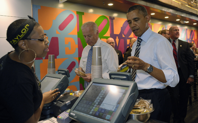 President Barack Obama tries to decide what kind of cookie to get as he and Vice President Joe Biden order lunch at Taylor Gourmet sandwich shop near the White House in Washington, Friday, Oct. 4, ...