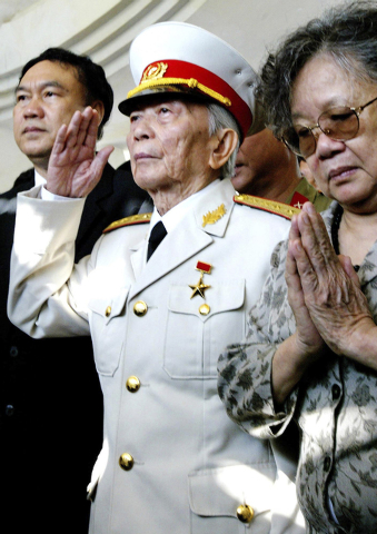 FILE - In this April 18, 2004 file photo, Gen. Vo Nguyen Giap salutes his fallen comrades at a shrine of the Dien Bien Phu's war cemetery in Dien Bien Phu, Vietnam. Officials say legendary Gen. Gi ...