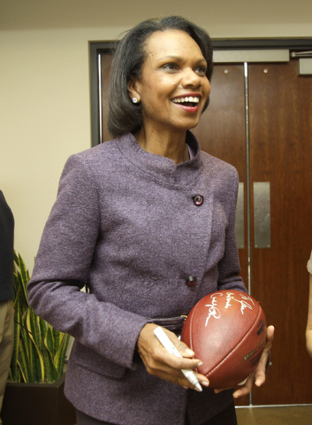 In this Oct. 10, 2010, file photo, former Secretary of State Condoleezza Rice laughs after autographing a football following her visit with the Cleveland Browns coaches and players at the team's N ...