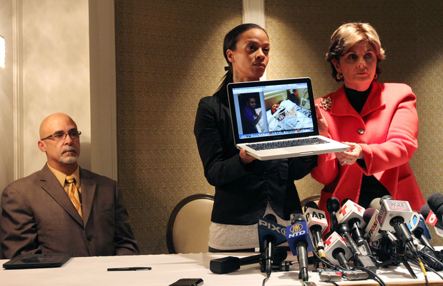 Dayana Mejia, center, and attorney Gloria Allred, right, hold up a laptop with images of Mejia's partner, Edwin Mieses Jr., during a news conference in New York, Friday, Oct. 4, 2013. Mejia was st ...