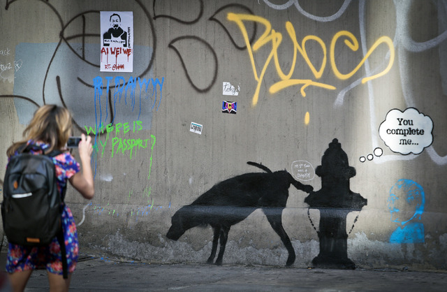 Graffiti by the secretive British artist Banksy, featuring a dog and a fire plug, draws attention on 24th Street, near Sixth Avenue in New York, on Friday, Oct. 4, 2013.  Banksy graffiti is turnin ...