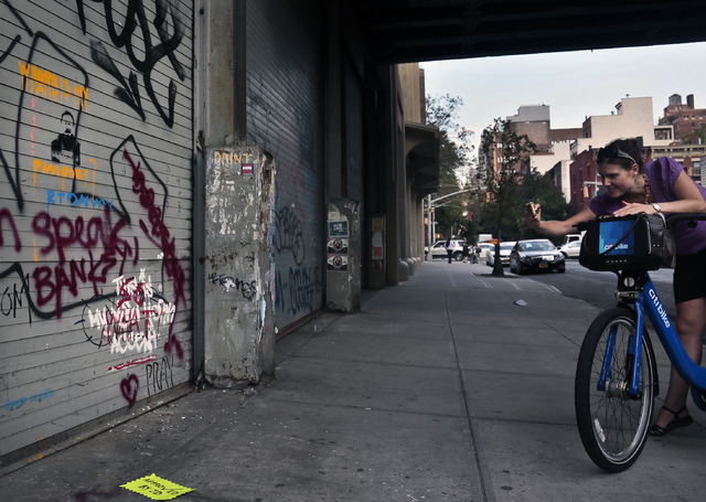 "A woman takes a cell phone picture of graffiti painted in white by the secretive British artist Banksy, already ""tagged"" over by another artist, on Friday, Oct. 4, 2013 in New York.  Ban ..."