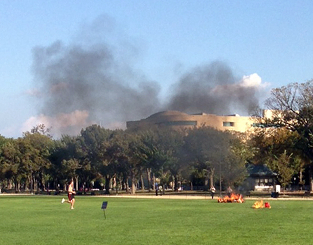 In this photo provided by Katy Scheflen, people run to a man who set himself on fire on the National Mall in Washington, Friday, Oct. 4, 2013. The reason for the self-immolation was not immediatel ...