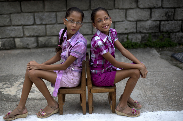 In this Sept. 29, 2013 photo, nine-year-old twin sisters Camila, left, and Carla Rodriguez pose for a portrait along their street in Havana, Cuba.  12 sets of twins live along two consecutive bloc ...