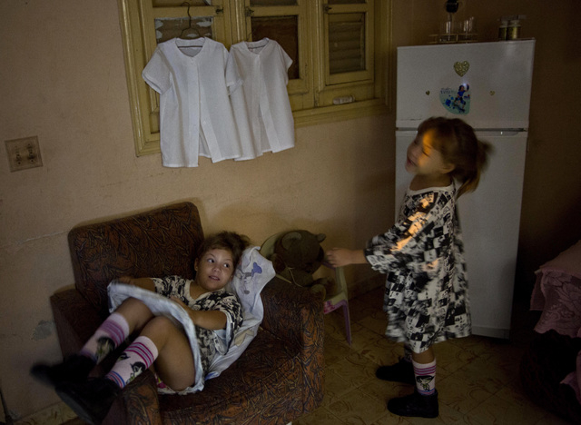 In this Sept. 23, 2013 photo, six-year-old twins Asley and Aslen Velazquez get ready for school in Havana, Cuba. Their mother Tamara said she never expected to have twins from her first pregnancy  ...
