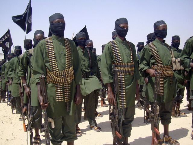FILE - In this Thursday, Feb. 17, 2011 file photo, al-Shabab fighters stand in formation with their weapons during military exercises on the outskirts of Mogadishu, Somalia. International military ...