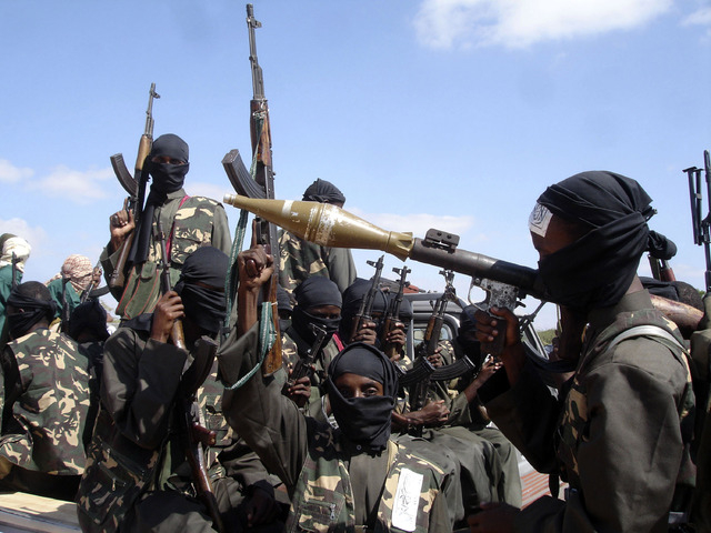 FILE - In this Dec. 8, 2008 file photo, armed al-Shabab fighters just outside Mogadishu prepare to travel into the city in pickup trucks after vowing there would be new waves of attacks against Et ...