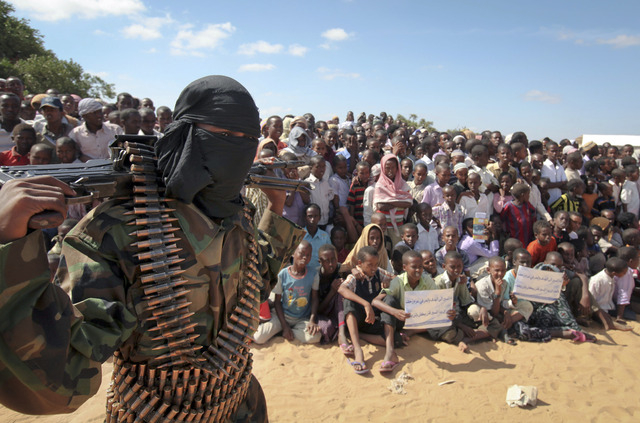 FILE - In this Monday, Feb. 13, 2012 file photo, an armed member of the militant group al-Shabab attends a rally on the outskirts of Mogadishu, Somalia. International military forces carried out a ...