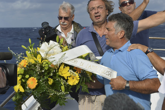 "Fishing boat captain Calosero Spalma, right, throws a wreath, with writing on a ribbon written in Italian ""Fishermen of Lampedusa"", into the sea to pay tribute to the victims of Thursday ..."