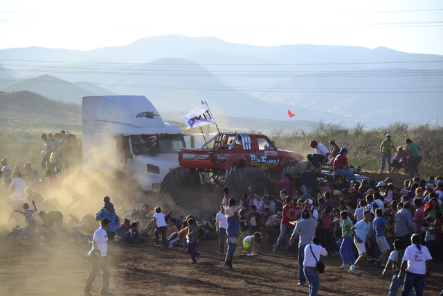 People run as an out of control monster truck plows through a crowd of spectators at a Mexican air show in the city of Chihuahua, Mexico, Saturday Oct. 5, 2013. According to authorities, at least  ...
