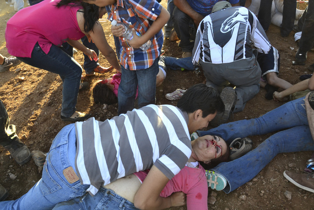 Injured people are treated after an out of control monster truck plowed through a crowd of spectators at a Mexican air show in the city of Chihuahua, Mexico, Saturday Oct. 5, 2013. According to au ...