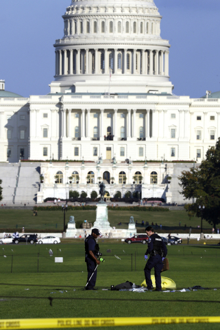 Law enforcement officers investigate the scene on the National Mall in Washington, where, according to a fire official, a man set himself on fire Friday, Oct. 4, 2013.  The official said the man w ...