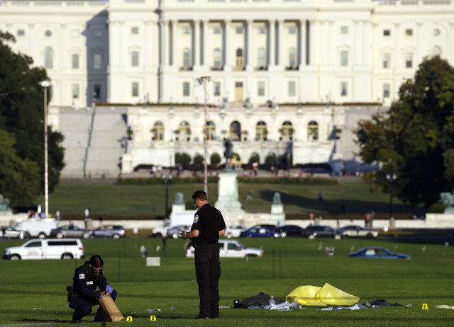 Police investigators gather evidence near where officials  said a man set himself on fire, on the National Mall, Friday, Oct. 4, 2013, in Washington. (AP Photo/Alex Brandon)