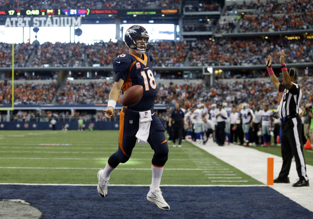 Denver Broncos quarterback Peyton Manning tosses the football after running in for a touchdown on a quarterback keep play late in the second quarter of an NFL football game against the Dallas Cowb ...