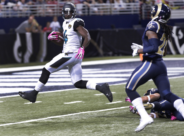 Jacksonville Jaguars wide receiver Justin Blackmon, left, runs past St. Louis Rams cornerback Janoris Jenkins after catching 67-yard pass for a touchdown during the first quarter of an NFL footbal ...