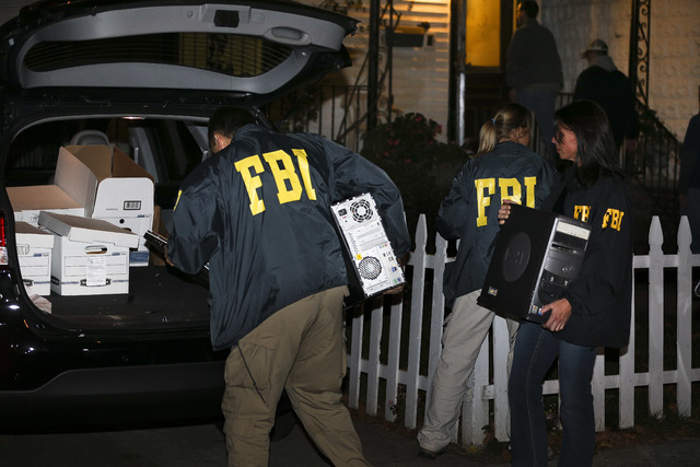 FBI agents remove evidence from the Brooklyn residence of Rabbi Mendel Epstein during an investigation, early Thursday, Oct. 10, 2013, in New York. Several defendants, including Epstein and anothe ...