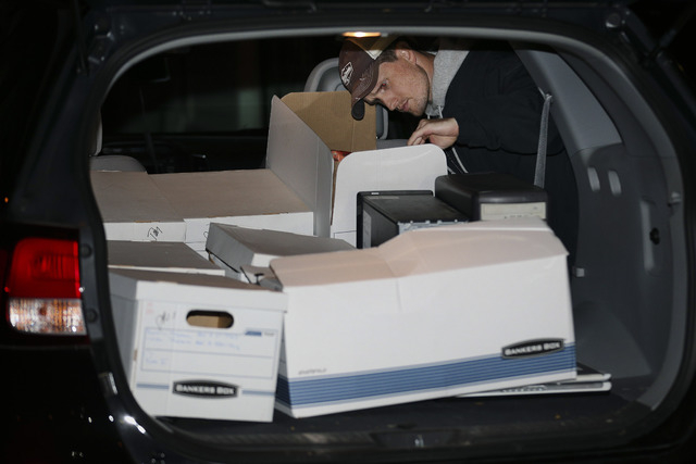 An FBI agent inspects evidence removed from the Brooklyn residence of Rabbi Mendel Epstein during an investigation, early Thursday, Oct. 10, 2013, in New York. Several defendants, including Epstei ...