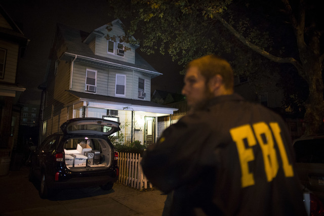 An FBI agent stands guard as evidence sits in the trunk of a vehicle at the Brooklyn residence of Rabbi Mendel Epstein during an investigation, early Thursday, Oct. 10, 2013, in New York. Several  ...
