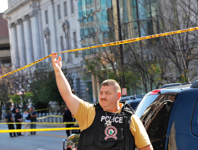 An Ohio County Sherriff Department deputy secures an area in front of the Federal Buildng in Wheeling, West Virginia Wedneday, Oct. 9, 2013, following a shooting outside the courthouse. West Virgi ...