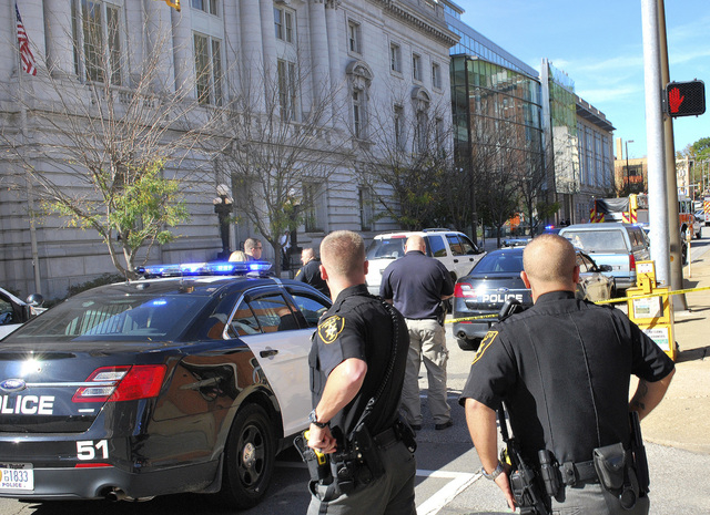 Local law enforcement officers secure an area in front of the Federal Buildng in Wheeling, WV, Wedneday, Oct. 9, 2013, following a shooting outside the courthouse.  The U.S. Marshals Services says ...