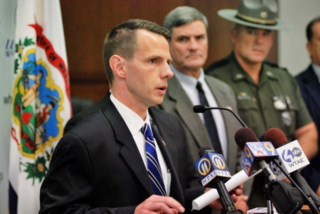 U.S. Attorney William J. Ihlenfeld II, foreground, speaks to the media Thursday, Nov. 10, 2013 in Wheeling, W. Va., about a shooting that took place outside the federal courthouse in downtown Whee ...
