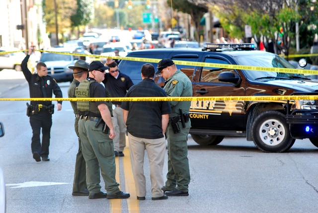 Authorities gather in front of the Federal Building in Wheeling, W.Va, on Wednesday, Oct. 9, 2013. West Virginia State Police say a man who fired shots at a federal courthouse in Wheeling has died ...