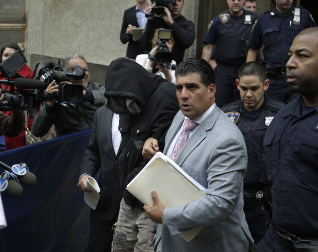 Wojciech Braszczok, center left, with face covered, leaves the courthouse in New York, Wednesday, Oct. 9, 2013. Braszczok, an undercover police detective, was charged with gang assault in a motorc ...