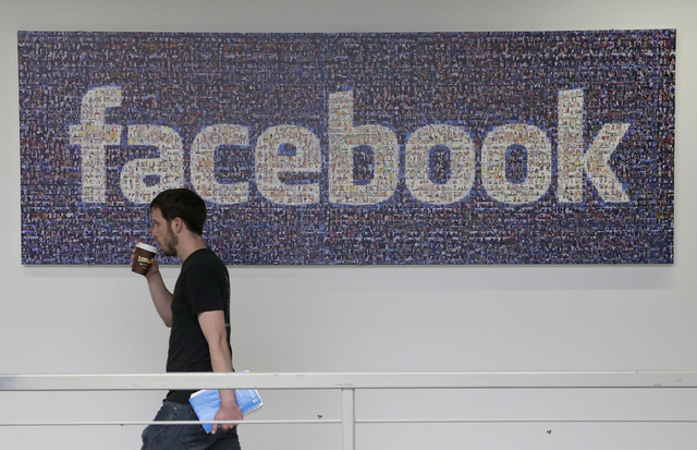 In this March 15, 2013 file photo, a Facebook employee walks past a sign at Facebook headquarters in Menlo Park, Calif. Facebook Inc. said Thursday Oct. 10, 2013, that it is removing a setting tha ...