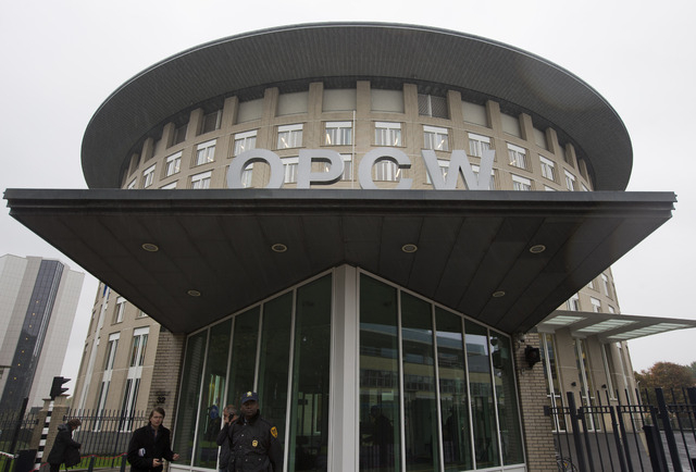 A security guard stands at the entrance at the headquarters of the world's chemical watchdog OPCW, in The Hague, Netherlands, Friday Oct. 11, 2013. The Organization for the Prohibition of Chemical ...