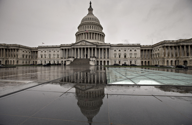 In this Oct. 7, 2013, photo. the U.S. Capitol is reflected during rain in Washington. Americans are finding little they like about President Barack Obama or either political party, according to a  ...