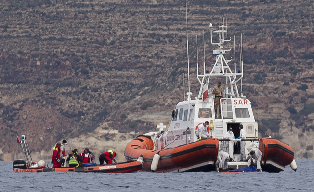 Italian Coast Guard personnel recover a body bag on their patrol boat in Lampedusa island, Italy, Tuesday, Oct. 8, 2013.  Italian divers have recovered more bodies from the wreck of a smuggler's s ...