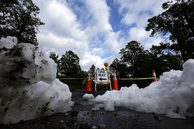 Freshly fallen snow is plowed into several piles creating another barrier at the main entrance to Grand Canyon National Park as the park remains closed to visitors on Thursday Oct. 10, 2013, in Gr ...