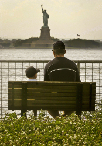 In this photo from June 20, 2006, Josef Morvai and his son Daniel Morvai, 4, view the Statue of Liberty from a park bench in Red Hook Garden Pier, in Brooklyn, N.Y. As the federal shutdown continu ...