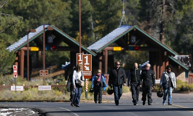 A group of motorcyclists from France walk back out from the main entrance to Grand Canyon National Park after they learned they were not allowed to enter the park on foot as it remains closed to v ...