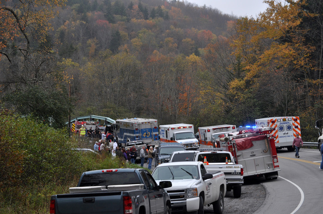 Emergency and rescue vehicles line the roadway leading to a crash site involving a truck carrying logs down Cheat Mountain on U.S. Route 250 and a train taking passengers on a scenic tour in rural ...
