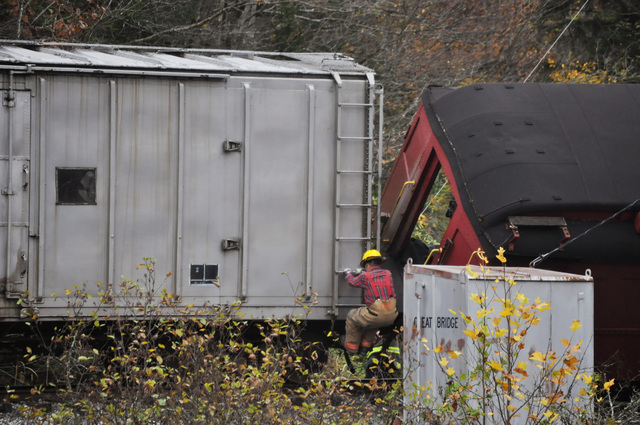 An emergency responder works to gain access to a passenger car that flipped on its side after a truck carrying logs down Cheat Mountain on U.S. Route 250 crashed into the train taking passengers o ...