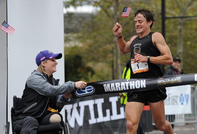 Boston marathon bombing survivor Erika Brannock holds an end of the tape at the finish line as runner David Berden wins the Baltimore marathon on Saturday, Oct. 12, 2013. (AP Photo/Gail Burton)