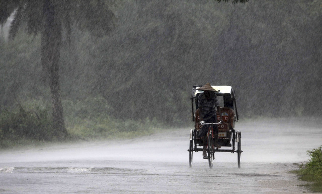 An Indian rickshaw puller carries people to a cyclone shelter near Chatrapur in Ganjam district about 200 kilometers  (125 miles) from the eastern Indian city Bhubaneswar, India, Saturday, Oct. 12 ...