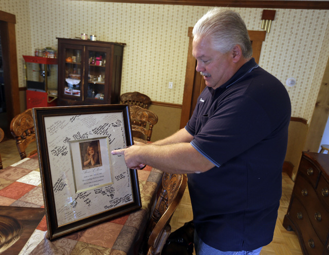 Tom Moore displays his daughter's graduation photo signed by her friends in his home in Terre Haute, Ind. on Thursday, Oct. 3, 2013. The Moores had continued to pay their daughter's cell phone bil ...