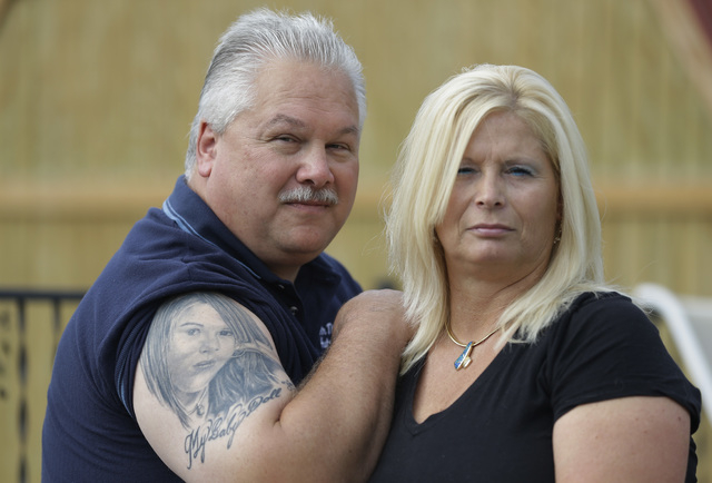 "Tom and Lisa Moore pose outside their home in Terre Haute, Ind. on Thursday, Oct. 3, 2013. Tom has a graduation photo of their daughter, Alexis, tattooed on his arm, ""so no one can take her a ..."