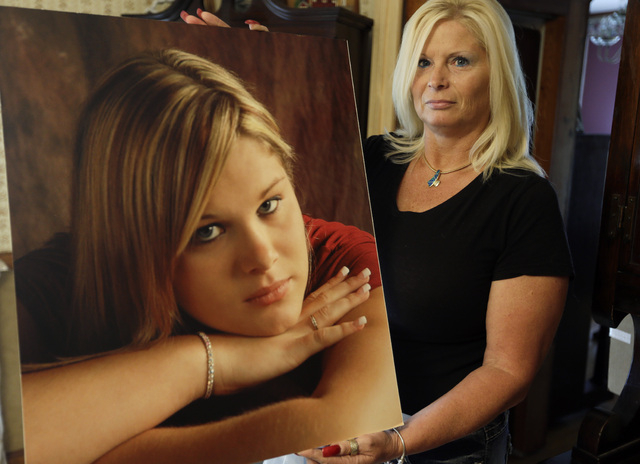 Lisa Moore displays a photo of her daughter, Alexis, in her home in Terre Haute, Ind. on Thursday, Oct. 3, 2013. The Moores had continued to pay their daughter's cell phone bill to preserve their  ...