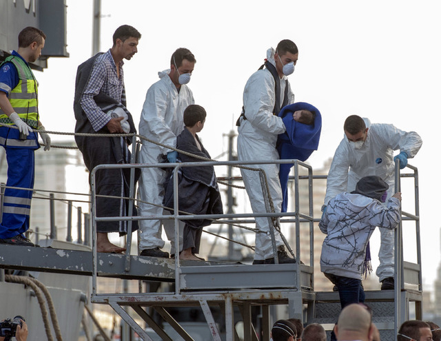 An officer holds a baby as migrants disembark from a Maltese Navy ship at the Valletta harbor, Malta, Saturday, Oct. 12, 2013. A Maltese ship has brought 143 survivors from a capsized smugglers' b ...