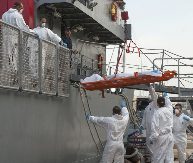 A body is being lowered down from a Maltese Navy ship at the Valletta harbor, Malta, Saturday, Oct. 12, 2013. A Maltese ship has brought 143 survivors from a capsized smugglers' boat to Malta whil ...