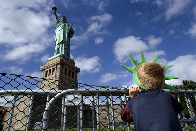 Jackson Blendowski, 6, of New Hampshire, peers up at the Statue of Liberty in New York Harbor, Sunday, Oct. 13, 2013, in New York. The Statue of Liberty reopened to the public after the state of N ...