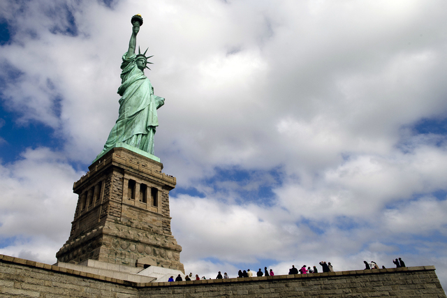 Tourists visit the Statue of Liberty in New York Harbor, Sunday, Oct. 13, 2013, in New York. The Statue of Liberty reopened to the public after the state of New York agreed to shoulder the costs o ...