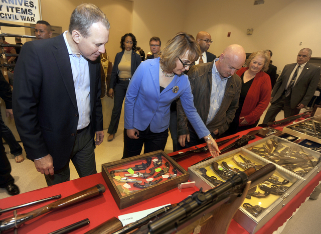 New York Attorney General Eric Schneiderman, left, former Arizona congresswoman Gabrielle Giffords, center, and her husband Mark Kelly tour the New EastCoast Arms Collectors Associates arms fair i ...
